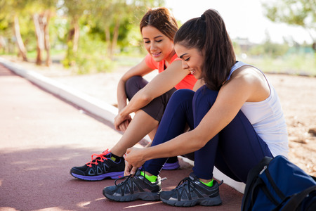 women friends: Female friends tying their shoes and getting ready to go for a run at a track