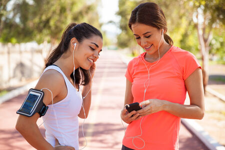 getting ready: Cute female runners getting ready and sharing songs before going for a run Stock Photo