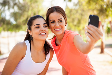 latin: Beautiful girls taking a selfie with a smart phone before going for a run outdoors Stock Photo