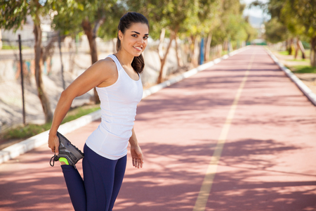 Gorgeous female runner stretching her legs before going for a run at the track