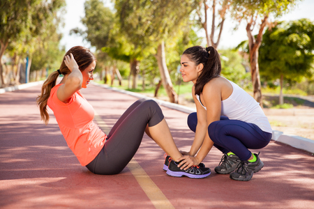 Two female friends working out together and doing some crunches outdoors photo