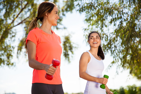 Beautiful young women walking outdoors while talking and carrying dumbbells photo