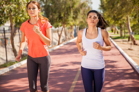 Cute young Hispanic women running together at a running track photo