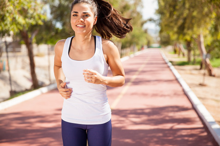 jogging track: Beautiful young brunette training at a running track and smiling