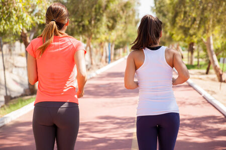 Rear view of a couple of female friends running together on a sunny day