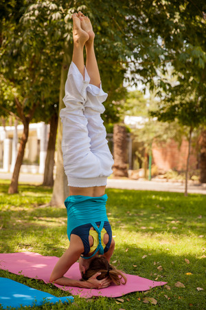headstand: Strong young woman practicing the headstand yoga pose at a park