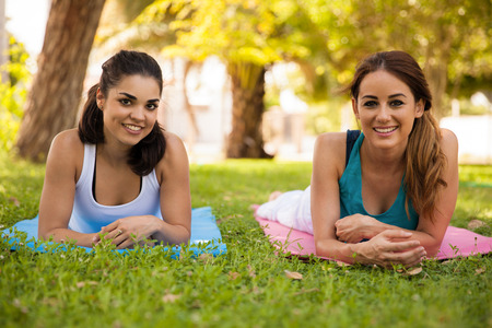 eye shade: Beautiful and happy friends hanging out and enjoying her yoga practice outdoors Stock Photo