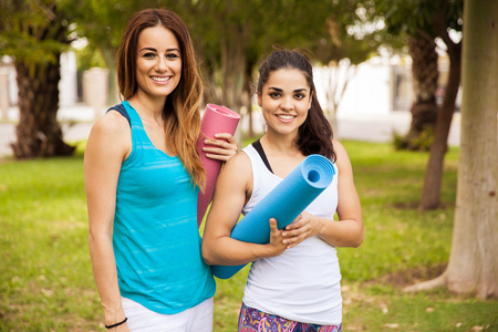 Portrait of a couple of beautiful young women carrying yoga mats and smiling Фото со стока