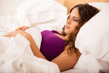 peacefully: Young and beautiful brunette sleeping peacefully and resting on a hotel bed