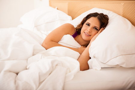 bed sheet: Young Hispanic woman trying to sleep on a large bed in a hotel room