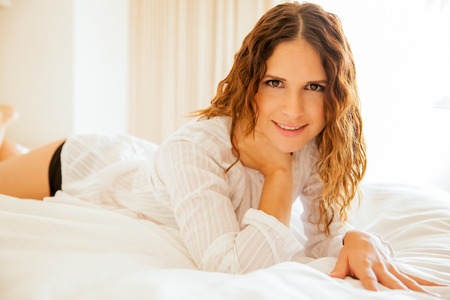 sleepwear: Cute Hispanic young woman with curly hair relaxing on her bed and smiling