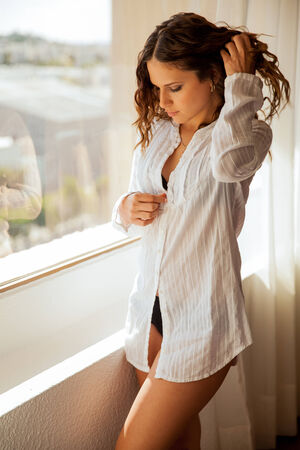 Beautiful young Hispanic brunette enjoying the view next to a window and taking her shirt off Stock fotó