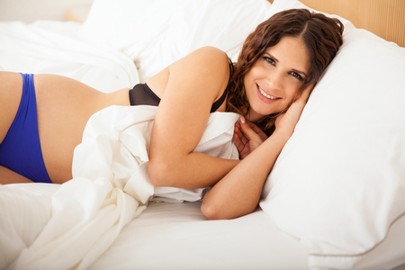 contact sheet: Happy young woman in underwear sleeping in her bed and covering herself with the bed sheets Stock Photo