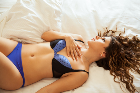 Beautiful young Hispanic woman in underwear lying on a bed and looking towards copy space photo