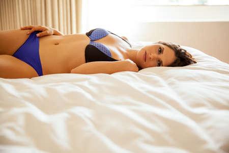 niñas en ropa interior: Brunette bastante joven en ropa interior acostada en una cama y mostrando su cuerpo Foto de archivo