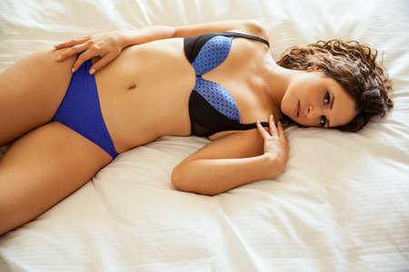 niñas en ropa interior: Mujer joven y coqueta hermosa con un cuerpo caliente acostado en una cama en su dormitorio Foto de archivo