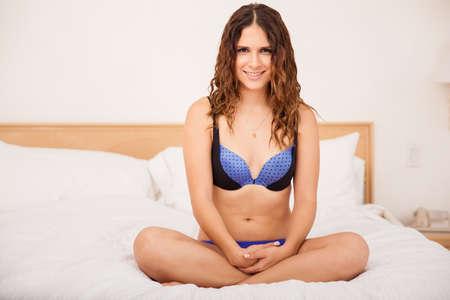 femme en sous vetements: Mignon jeune femme hispanique dans ses sous-vêtements assis sur un lit dans un hôtel et souriant