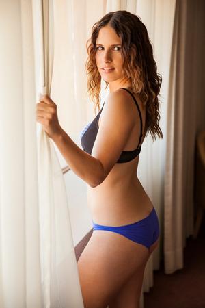 femme en sous vetements: Portrait d'une jeune femme magnifique montrant son corps tout en se tenant à côté d'une fenêtre en sous-vêtements