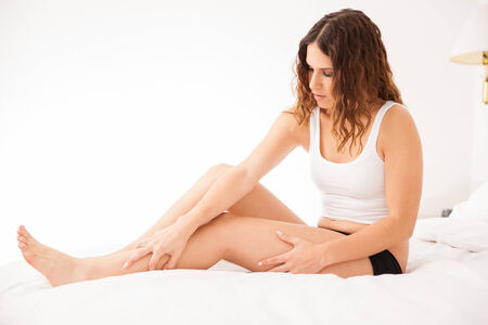 Cute Hispanic brunette touching her smooth legs after removing all hair photo