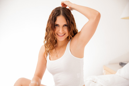 Portrait of a beautiful young woman showing her smooth and hairless armpit and smiling photo