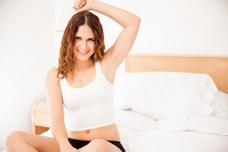 axilla: Gorgeous young woman raising her arm and showing her smooth and hairless armpits Stock Photo