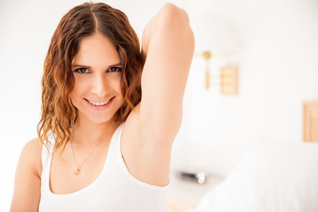 armpits: Closeup of a beautiful young Hispanic woman raising her arm and showing her smooth armpits