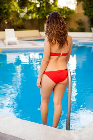 Full length portrait of a sexy girl in a bikini going inside a pool photo