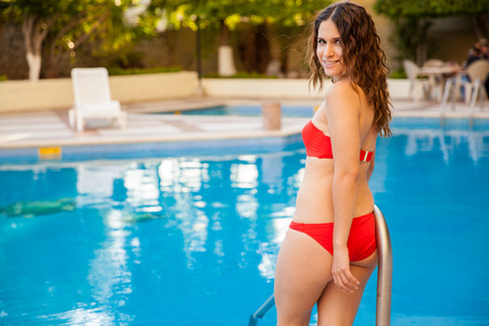 Happy young woman wearing a bikin and about to go inside a pool