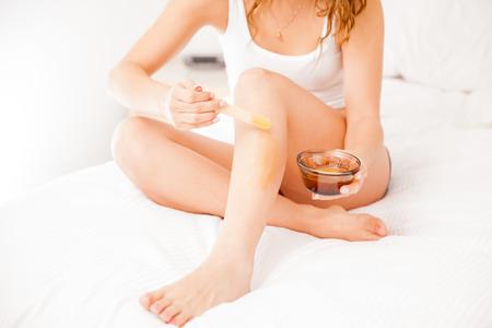 beine spreizen: Junge Frau spreding etwas Wachs auf ihre Beine mit einem Stock, um ihr Haar zu entfernen Lizenzfreie Bilder