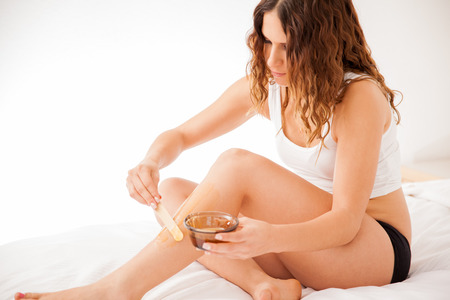 beine spreizen: Schöne junge Brünette verbreiten einige heiße Wachs auf ihre Beine, um alle Haare zu entfernen Lizenzfreie Bilder