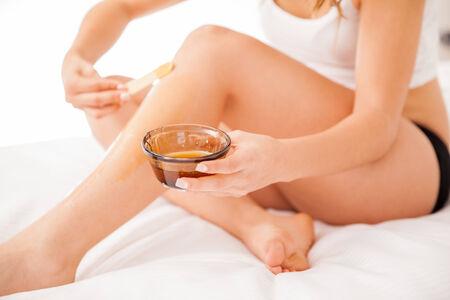 beine spreizen: Junge Frau mit schönen Beinen Putting etwas Wachs auf sie alle Haare zu entfernen Lizenzfreie Bilder