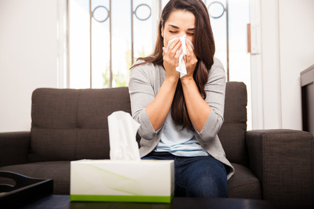 Beautiful young Hispanic woman with a bad cold blowing her nose at home
