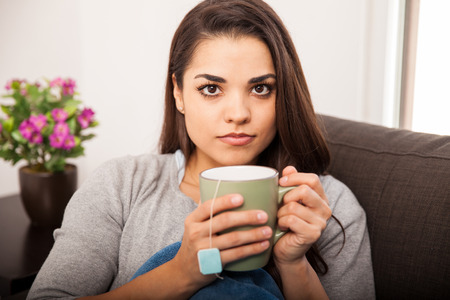 Portrait of a beautiful young Hispanic woman covered in a quilt and drinking hot tea photo