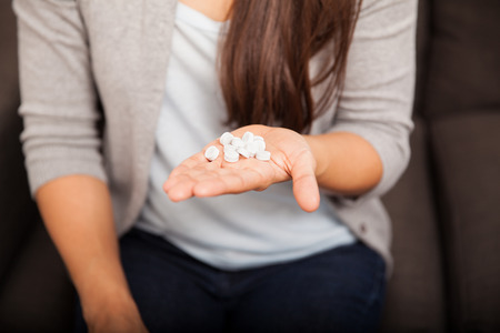 Closeup of a young woman holding too many pills in her hand at home