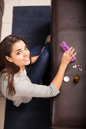 Cute young Latin woman organizing and sorting some of her pills at home and smiling photo