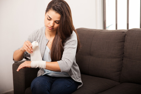 cut wrist: Portrait of a pretty young woman putting on a bandage on her twisted wrist Stock Photo