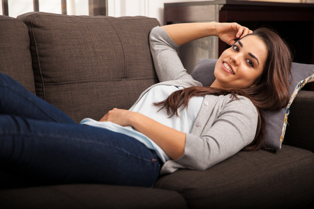 woman on couch: Beautiful young brunette relaxing and laying on a couch at home and smiling
