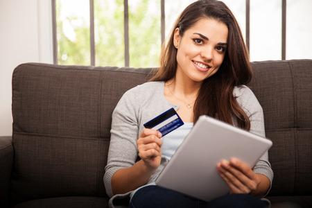tarjeta de credito: Muchacha magn�fica con su Tablet PC y una tarjeta de cr�dito para comprar algunas cosas en l�nea Foto de archivo