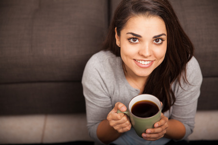 Gorgeous young woman enjoying a cup of coffee at home and smiling