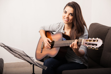 Gorgeous young brunette playing her favorite song with her guitar at home 写真素材