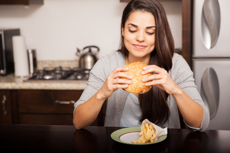 latin food: Beautiful young brunette about to bite a delicious hamburger at home