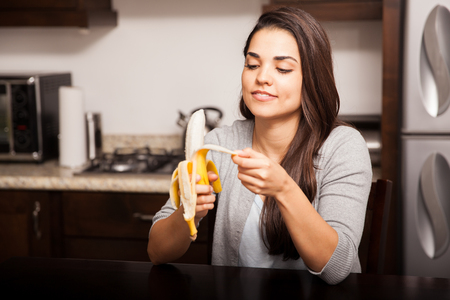 banana: Pretty young brunette peeling a banana before eating it while sitting in the kitchen