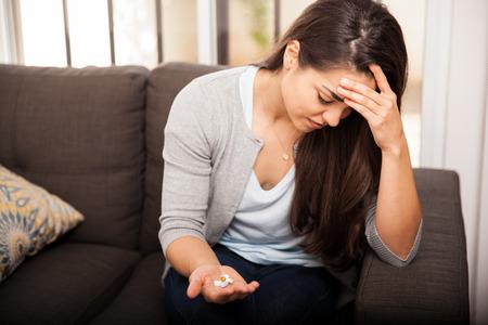 aspirin: Beautiful Hispanic young woman suffering from a headache and taking some aspirin Stock Photo