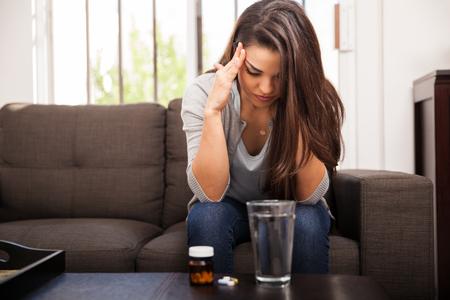 Mujer latina joven que tiene un dolor de cabeza y tomar una aspirina para sentirse mejor
