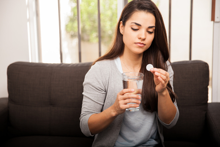 antacid: Beautiful young woman with indigestion about to take an antacid to feel better