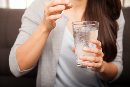 antacid: Closeup of a young woman dropping an antacid on a glass of water Stock Photo