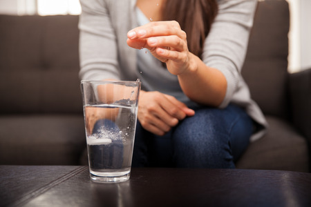 indigestion: Closeup of a young woman dropping an effervescent antacid in a glass of water