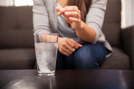 hangover: Closeup of a young brunette watching an antacid dissolve before drinking Stock Photo