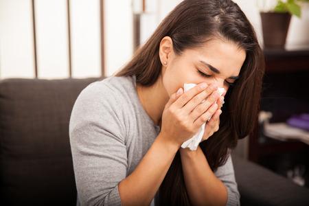 Portret cute młoda brunetka dmuchanie jej nosa po przeziębienia