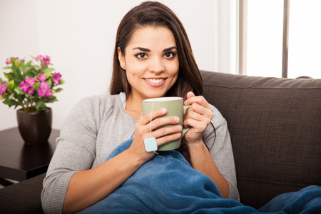 Cute young brunette drinking hot tea and smiling while relaxing in her couch photo